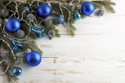 Christmas background with silver pinecone and blue ornaments.