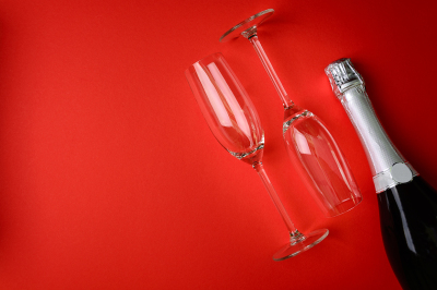 Bottle of champagne with wineglass lying on red paper background