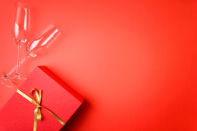 Wineglasses for champagne and gift box lying on red paper background.