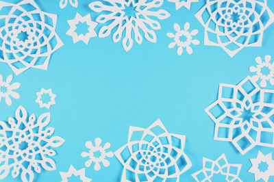 Paper snowflakes on blue background. Top view. Christmas decoration