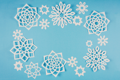 Paper snowflakes on blue background. Top view. Christmas decoration.