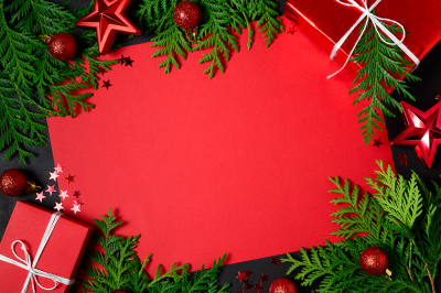 Christmas frame of red gift boxes, fir branches, confetti