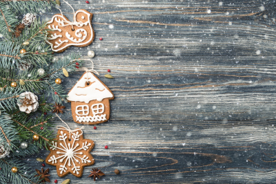 Christmas Frame of Gingerbread cookies on spruce over snowy wooden bac