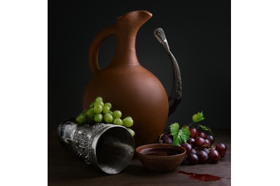 cup of wine pitcher drinking horn and grapes on a wooden table