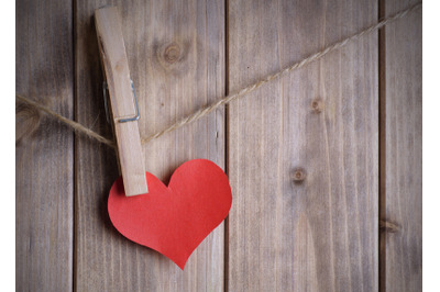 red heart made of paper with clothespin hanging on a rope and wooden p
