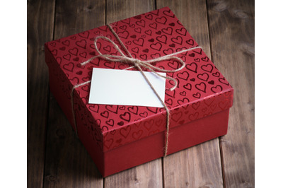 red gift box (package) in hearts with  card on old wooden background.