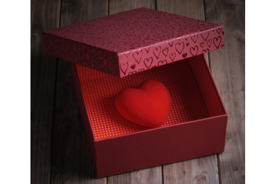 Heart in a gift box on an old wooden table, love concept