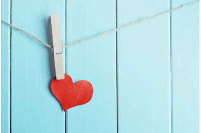 red heart made of paper with clothespin hanging on a rope and wooden blue planks background