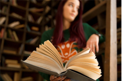 young girl reading a book in the library