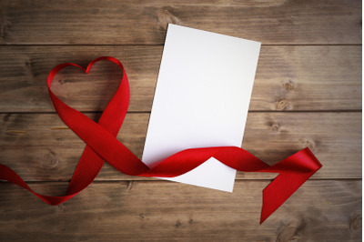 Valentines day heart shaped red ribbon and blank greeting card over wo
