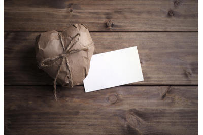 Heart wrapped in brown kraft paper with a note, on wooden background