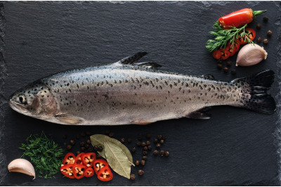 Fresh trout fish with spices and seasonings on a cutting board