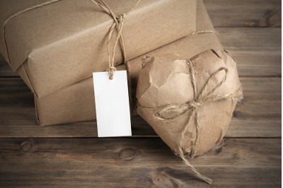 Heart and box wrapped in brown kraft paper on wooden table