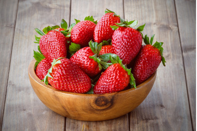 a bunch of ripe strawberries in a wooden bowl on the table
