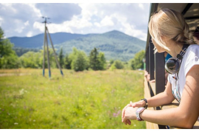 Young beautiful girl travels by narrow-gauge railway in the Ukraine