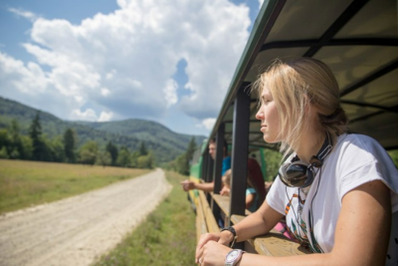 A young girl travels by old train in the  Carpathians.