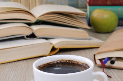A cup of coffee on the table against the background of an open book with a notebook and a stack of books