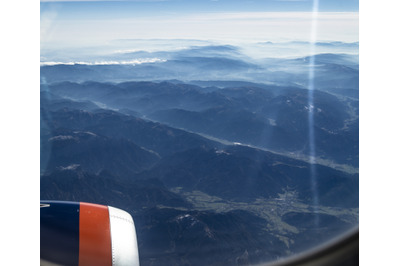 Looking through the window of the plane during the flight to the snow-