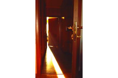 A beam of light falling on the floor through the open door in the room
