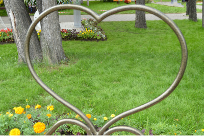Metal pattern heart symbol, look through the heart on the grass, Park,