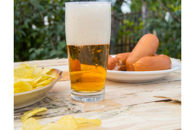 Beer in a glass with foam, sausages, chips on boards in the garden, Ok