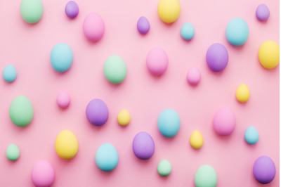 Pastel colored Easter eggs pattern on pink background