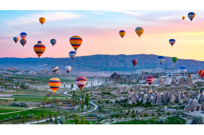 Colorful hot air balloons flying over rock landscape