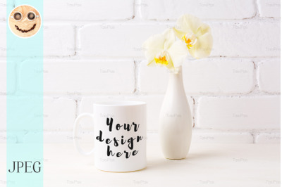 White coffee mug mockup with soft yellow orchid in vase
