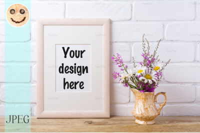 Wooden frame mockup with chamomile and purple flowers in golden pitche
