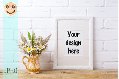 White frame mockup with chamomile and grass in golden vase