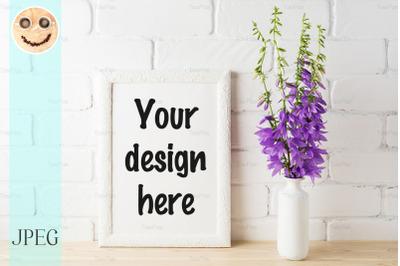 White frame mockup with purple campanula bouquet near brick wall