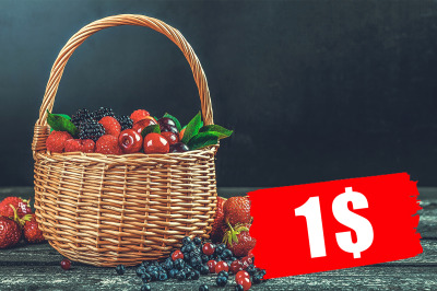 Fresh forest berries in basket on black wooden background with copy sp