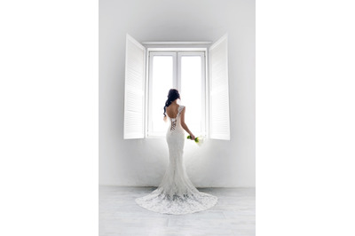 Bride in a white room by the window