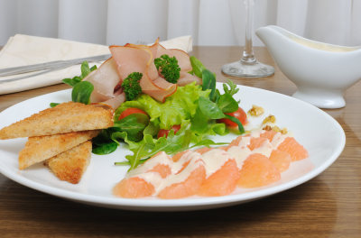 Salad mix with cherry tomatoes and ham with, toast with grapefruit cream sauce