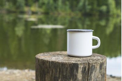 White enamel mug mockup with tree stump.