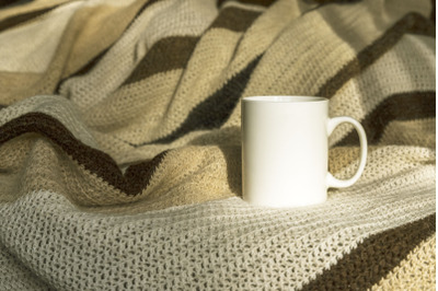 White coffee mug mockup with striped blanket.