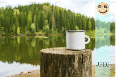 White campfire mug mockup with river bank view.