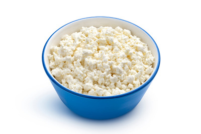 Cottage cheese in blue bowl isolated on white background