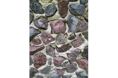Gray stone wall background, mosaic stonewall rubble facade closeup