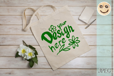 Tote bag mockup with beige notepad.