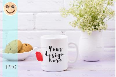 White coffee mug mockup with tender green flowers.