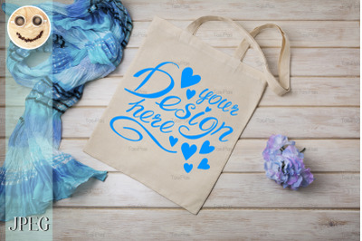 Tote bag mockup with blue scarf and flower.
