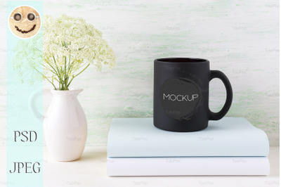 Black coffee mug mockup with books and tender white flowers.
