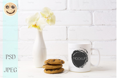 White coffee mug mockup with soft yellow orchid in vase and cookies