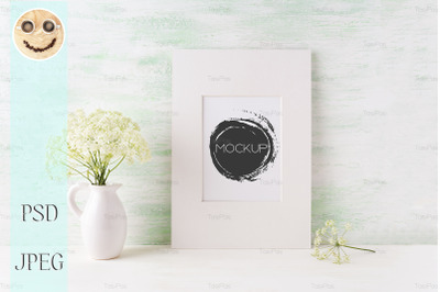 Easy white frame mockup with tender wild flowers in pitcher.