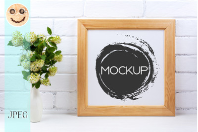Square wooden picture frame mockup with white spirea