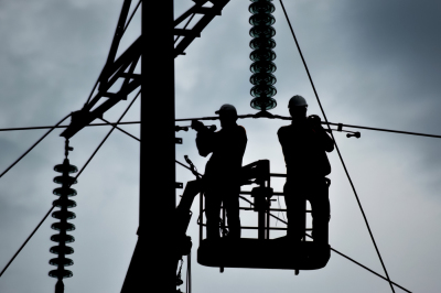 Photo: Silhouette of electricians working on the background of the cloudy sunset.