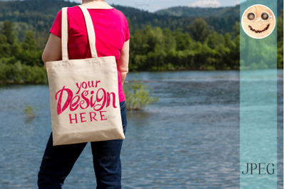 Woman in red tee holding tote bag mockup