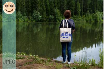 Woman carrying tote bag on the lake shore, mockup.