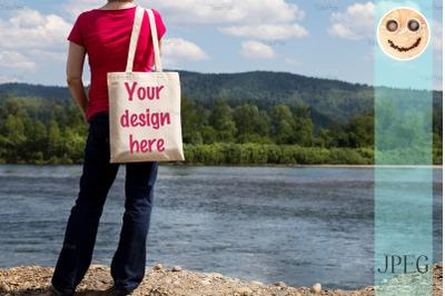 Woman holding eco bag mockup, river view.